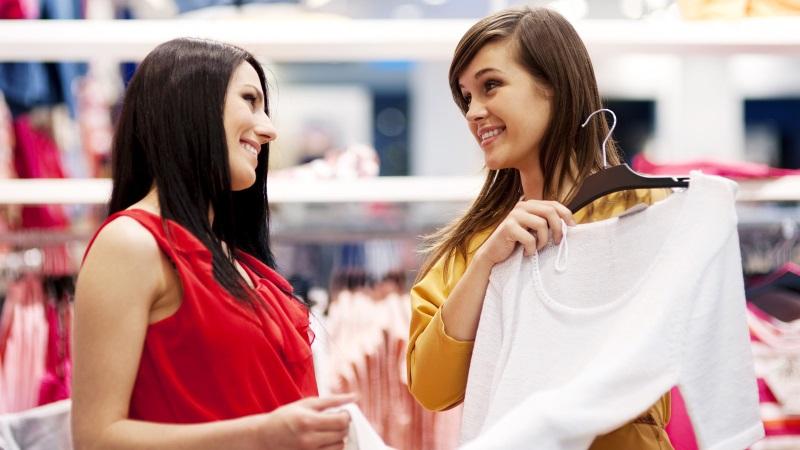 duas mulheres a escolherem uma blusa durante os saldos