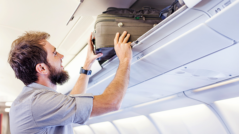Homem a guardar a bagagem de mão na cabine do avião