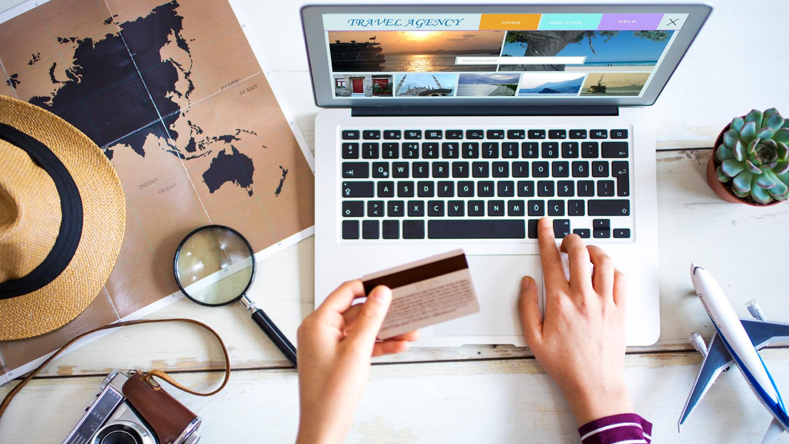 pessoa a planear viagem enquanto pesquisa no computador com mapa do mundo e fotografias