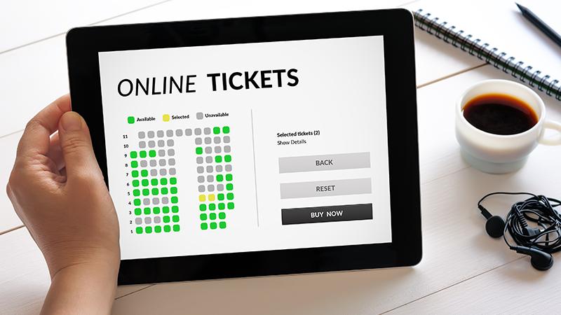 Pessoa a segurar um tablet enquanto compra bilhetes online