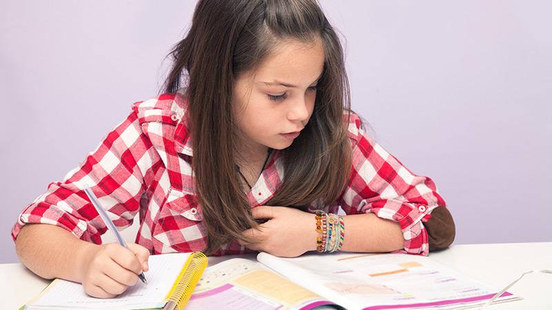 rapariga a estudar com um livro escolar