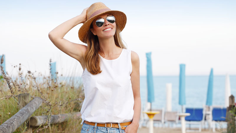 Mulher de óculos escuros e chapéu a apanhar sol