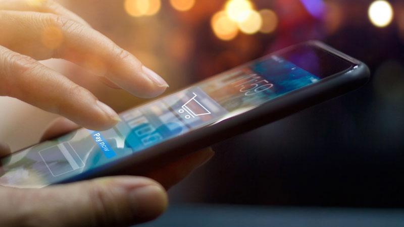 mão a aceder a telemóvel para comprar serviços online