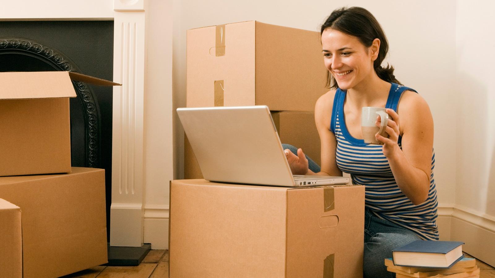 Mulher rodeada por caixas de mudanças, a comparar tarifários de TV, net e voz para a nova casa